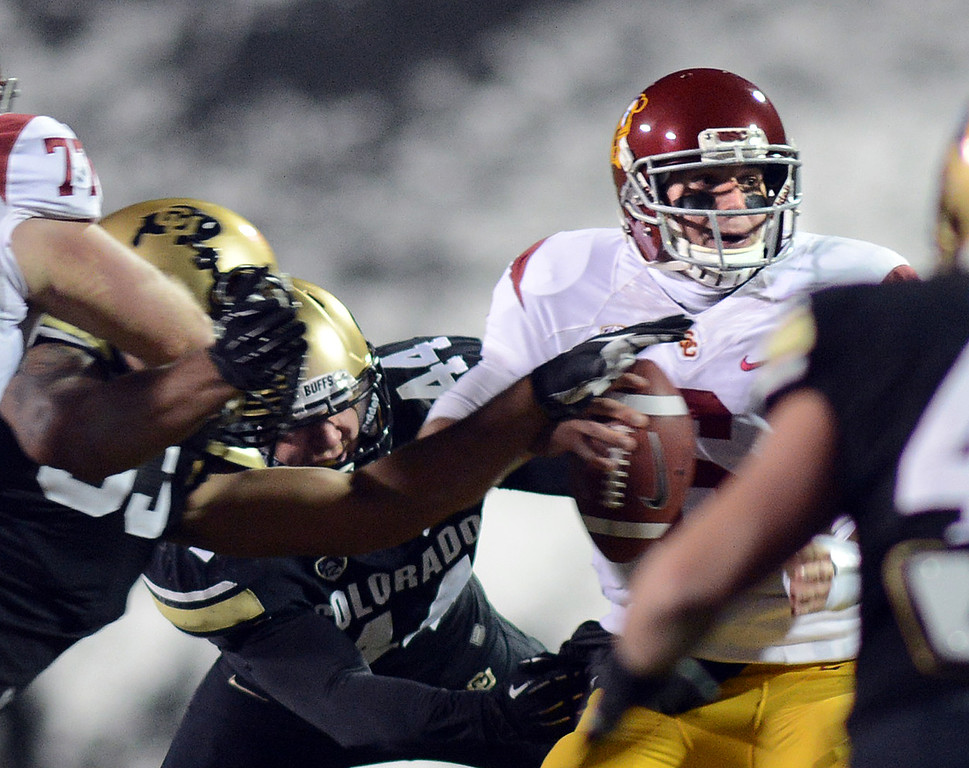 . Samson Kafovalu, left, and Addison Gillam of CU, sack USC QB, Cody Kessler during the first half of the November 23, 2013 game in Boulder, Colorado.  Cliff Grassmick / November 23, 2013
