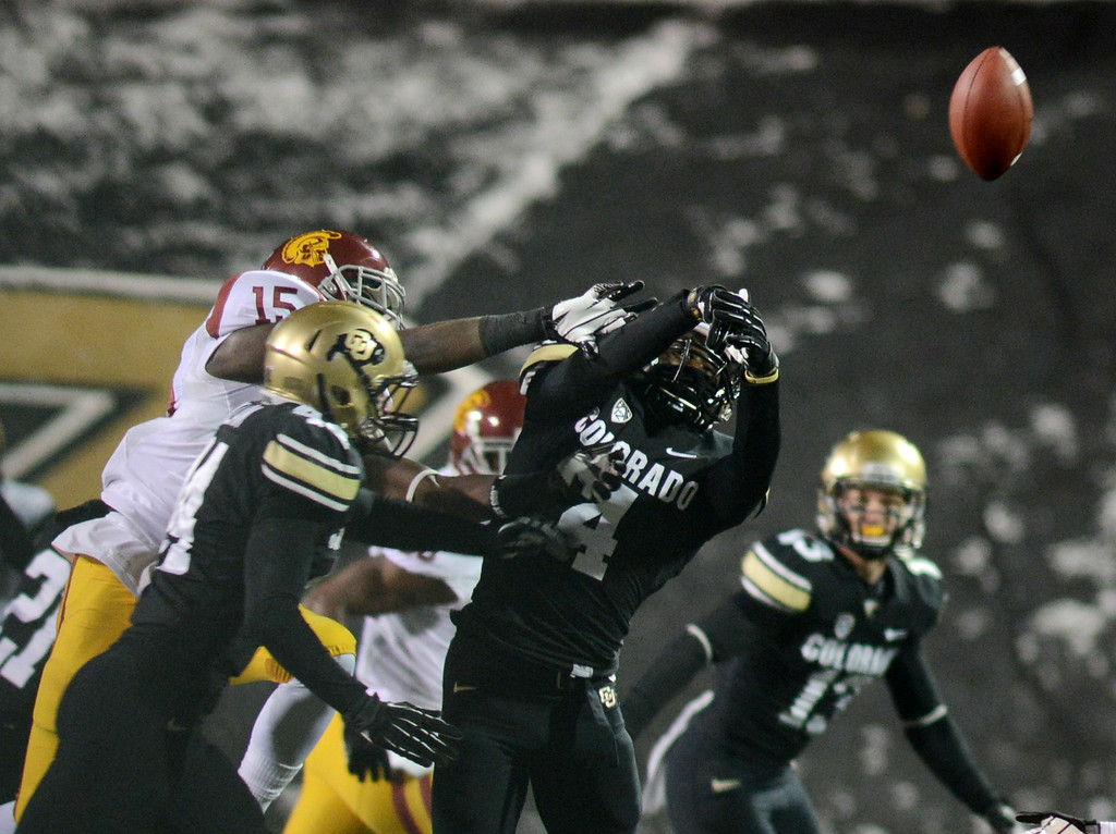 . Chidobe Awuzie (4) of CU breaks up a pass for Nelson Agholor of USC during the first half of the November 23, 2013 game in Boulder, Colorado.  Cliff Grassmick / November 23, 2013