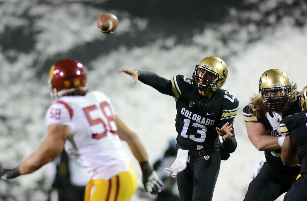 . Sefo Liufau fires out a pass against USC. JR Tavai is defending for USC during the first half of the November 23, 2013 game in Boulder, Colorado.  Cliff Grassmick / November 23, 2013