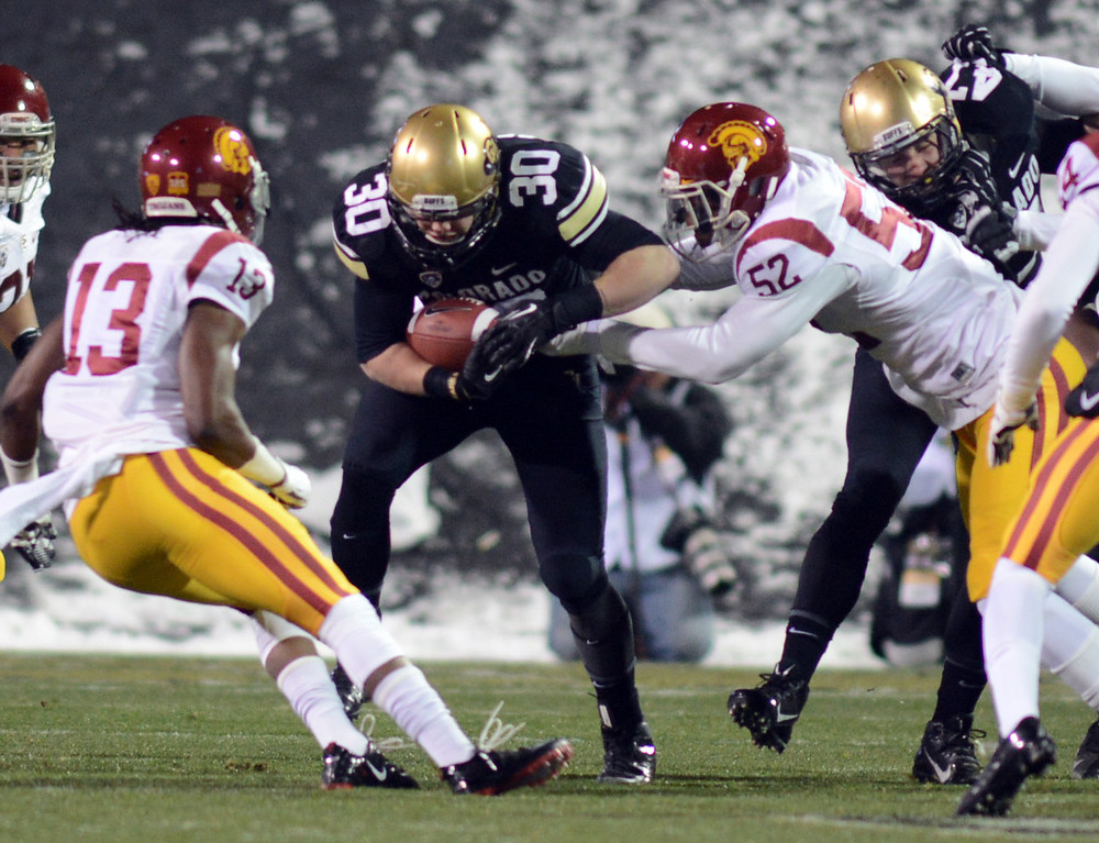 . Ryan Severson of CU returns a kickoff and is tackled by Quinton Powell (52) of USC during the first half of the November 23, 2013 game in Boulder, Colorado.  Cliff Grassmick / November 23, 2013