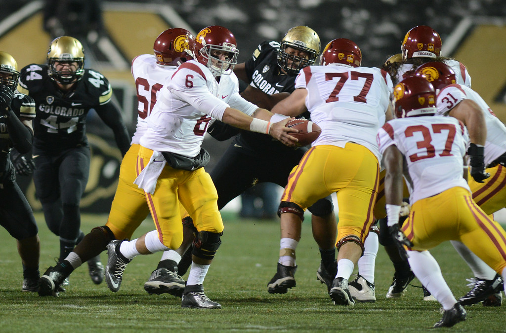 . Cody Kessler of USC hands the ball off to Javorius Allen of USC during the first half of the November 23, 2013 game in Boulder, Colorado.  Cliff Grassmick / November 23, 2013