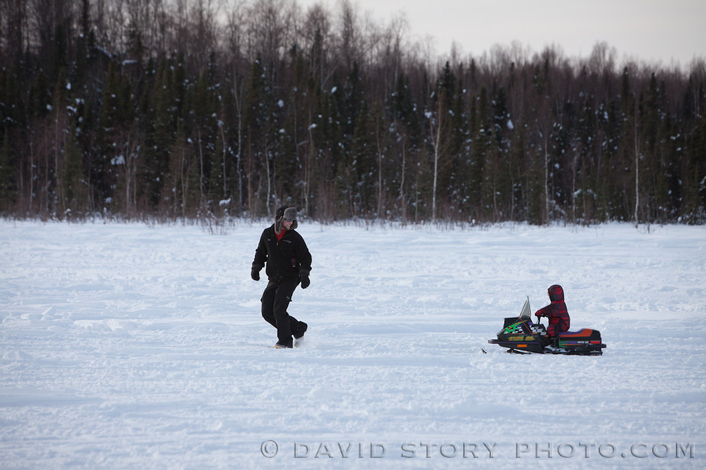Dad coaches his child on snowmachining from an early age.