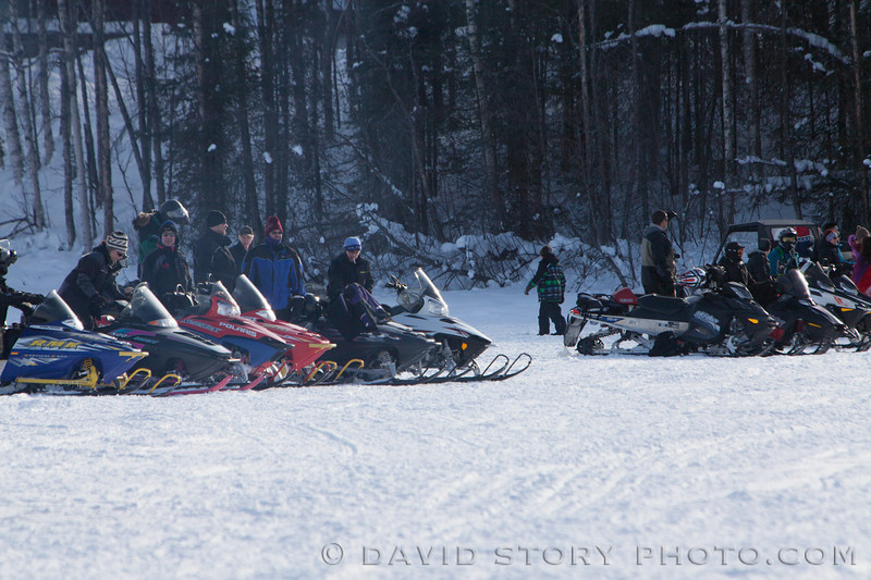 Snowmachines line the race path along Long Lake.