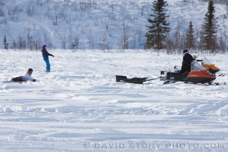 Kids tow each other on snowboards and skis behind snowmachines.