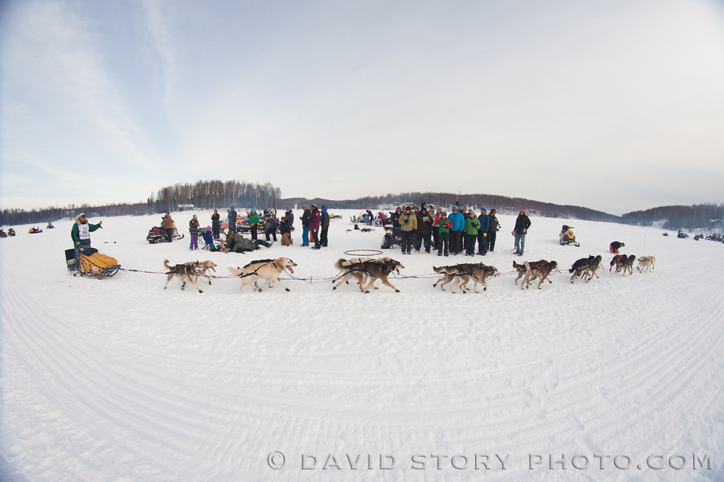 Matt Giblin passes by a crowd of fans on Long Lake at the 2013 Iditarod.