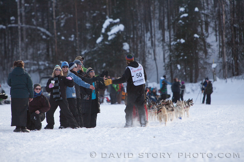 Fanned out hands find high fives from musher Michael Ellis.