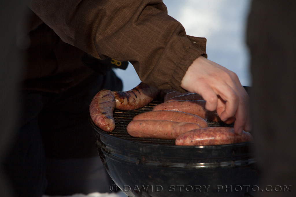 A spectator turns sausages on the grill while watching the 2013 Iditarod.