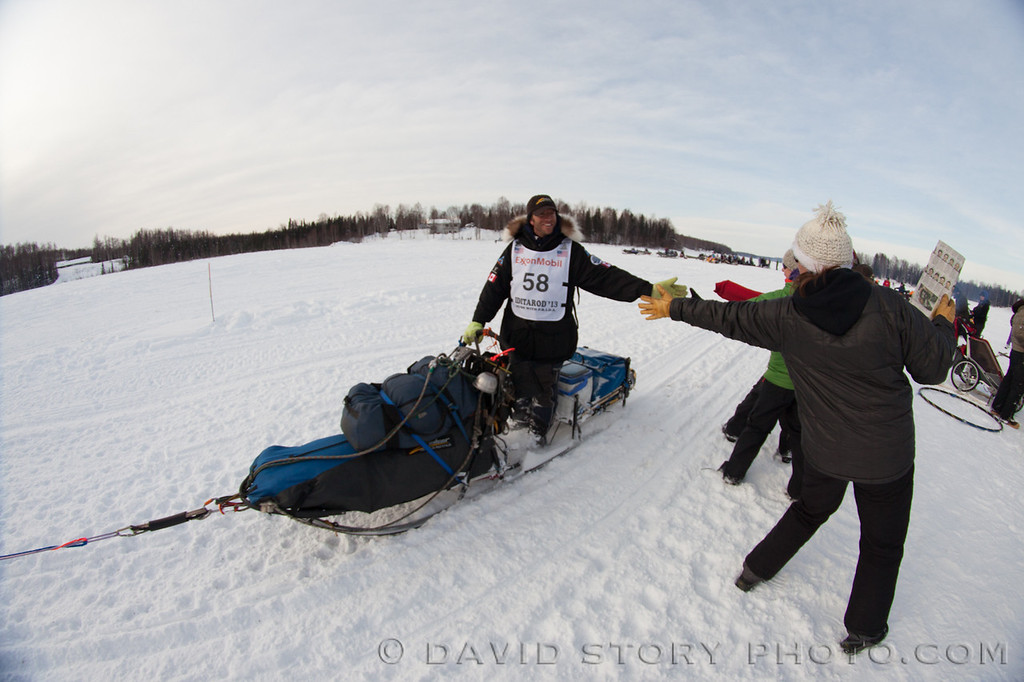Aaron Peck extends a hand to greet fans at the 2013 Iditarod.