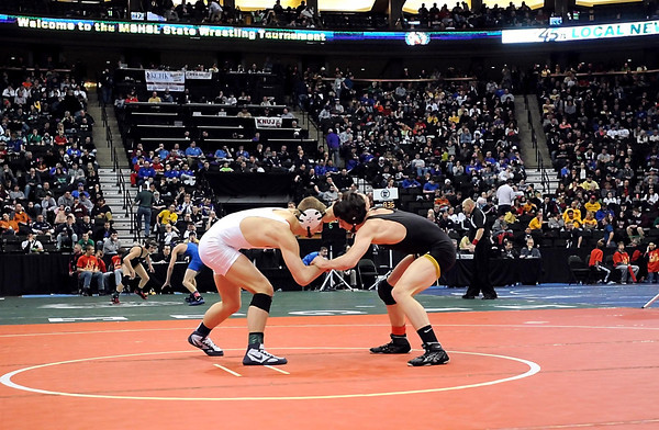 Sibley East's Hunter Retzlaff (in black) and United South Central's Derek Herman wrestle during their State Class A 138 pound quarterfinal match Friday at the Xcel Energy Center in St. Paul.