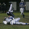 RYAN HUTTON/ Staff photo. Lawrence's Justin Rivera (16) tumbles over a Salem defender  after catching a pass in the second quarter of Wednesday night's game in Salem, NH.