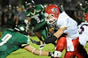Hardin-Jefferson's Jared Gleseke runs the ball for a short gain with East Chambers' Charlie Edwards to make the tackle at Buccaneer Stadium Friday night. Photo provided by Drew Loker.