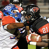 Memorial's Corey Dauphine, 21, gives Bruin's DeVante Williams, 55, a stiff arm to the eye at Memorial High School Stadium Friday night. Photo by Drew Loker.