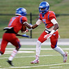 On the opening return kickoff, West Brook Bruin Isaac Aubrey, 2, hands off the return to Cameron McKinney, 7, at the Carroll Thomas Stadium Friday night. Photo by Drew Loker.