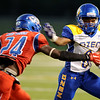 Ozen Panther Calvin Tyler, 8, tries to avoid West Brook Bruin Desmond Veals, 24, and Corry McGill, 23, at the Carroll Thomas Stadium Friday night. Photo by Drew Loker.