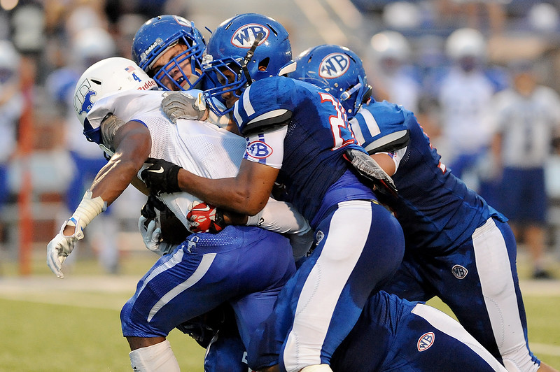 A host of West Brook Bruins stop the Taylor Mustang running game for a loss at the Carroll Thomas Stadium. Photo by Drew Loker.