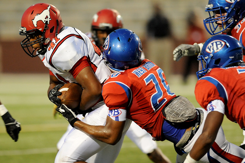 West Brook Bruins Delano Hawthorne, 26, grabs a hold of a North Shore Mustang at the Carroll Thomas Stadium September 26, 2014. Photo by Drew Loker.