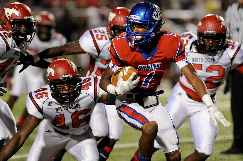 West Brook Bruin Keith Corbin, 1, looks for a way out from a host of North Shore Mustangs closing in at the Carroll Thomas Stadium September 26, 2014. Photo by Drew Loker.