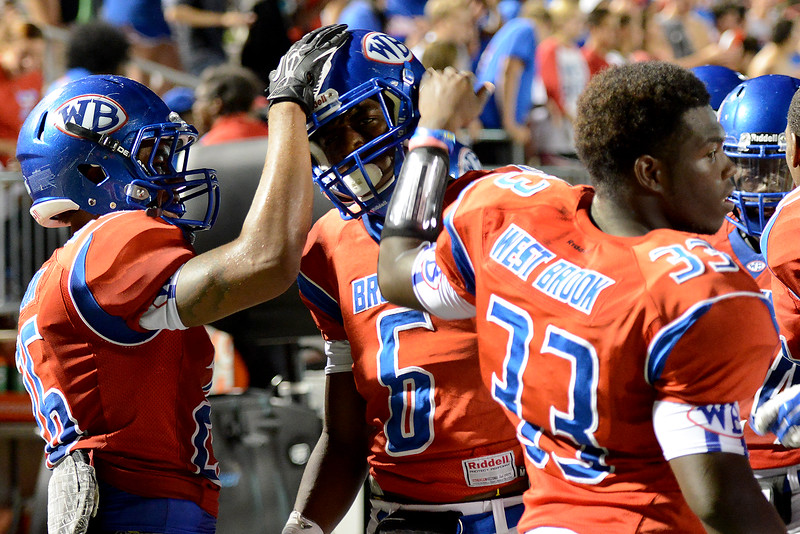 West Brook Bruins Delano Hawthorne, 26, and D'angelo Godfrey, 33, congratulate Innis Gaines, 6, after an interception and nice gain during the match up against the North Shore Mustangs at the Carroll Thomas Stadium September 26, 2014. Photo by Drew Loker.