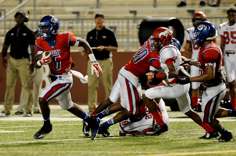 West Brook Bruin Innis Gaines, 6, dodges several tackles for a nice gain after an interception against the North Shore Mustangs at the Carroll Thomas Stadium September 26, 2014. Photo by Drew Loker.