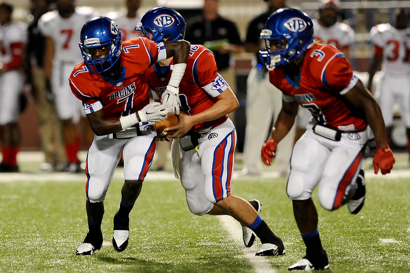 West Brook Bruin Cameron McKinney, 7, assists with the quaterback keeper during the match up against the North Shore Mustangs at the Carroll Thomas Stadium September 26, 2014. Photo by Drew Loker.