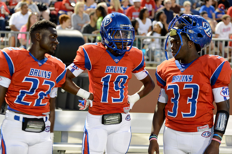 West Brook Bruins Isaac Cheatham, 22, Nate Paker, 19, and D'angelo Godfrey, 33, discuss the game against the North Shore Mustangs at the Carroll Thomas Stadium September 26, 2014. Photo by Drew Loker.