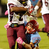 Central Jaguar Exavier Jones, 2, tries to escape from Lumberton Raider Jarrod Boutwell, 22, at Lumberton High School October 3, 2014. Photo by Drew Loker