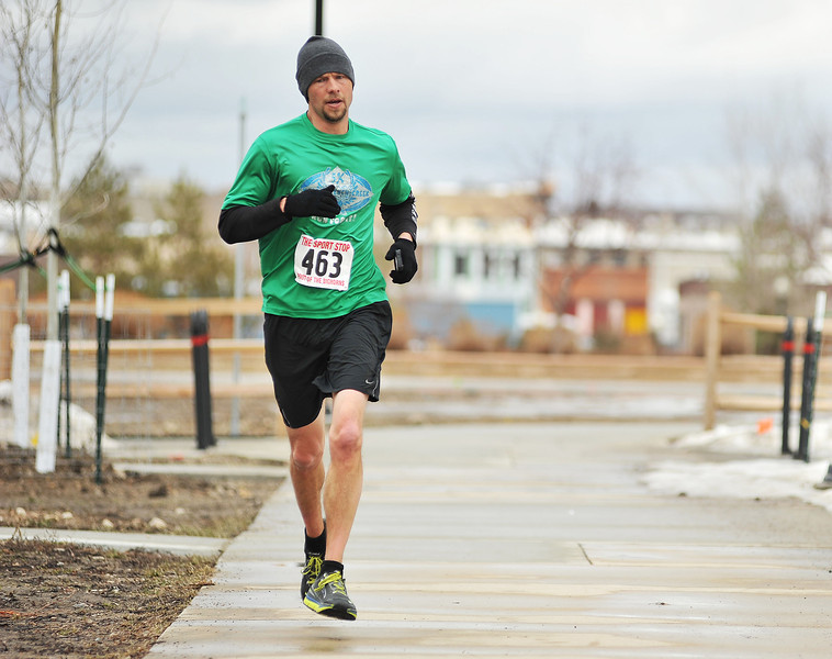 """Chris Newton runs up the side walk entering Kendrick Park during the Sheridan Jaycees """"Run 'Till You're Green"""" fun run event. Newton finished first in the 5K overall with a time of 19:28.460."""