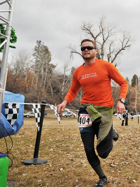 """Clay Stoner crosses the finish line placing first in the 10K race during the Sheridan Jaycees """"Run 'Till You're Green"""" fun run event."""