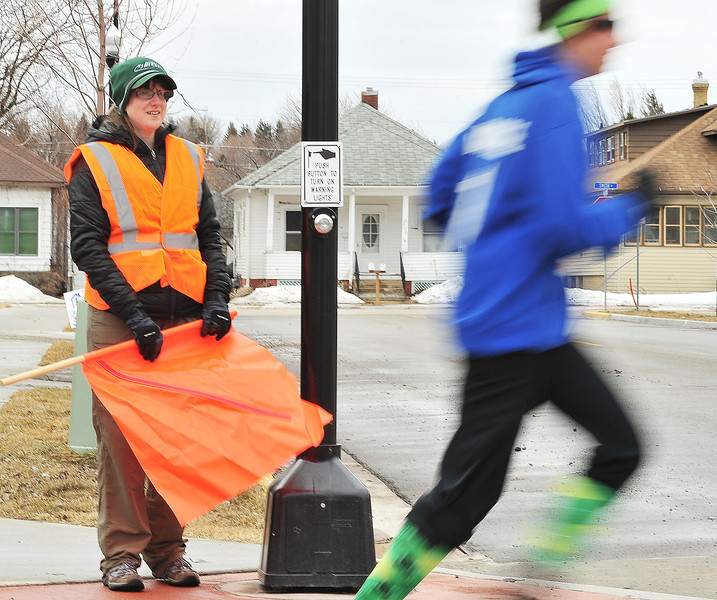 """Billie Chapman of the Sheridan Jaycees mans the crossing on Jefferson Street as a 5K runner passes by during the """"Run 'Till You're Green"""" fun run event."""