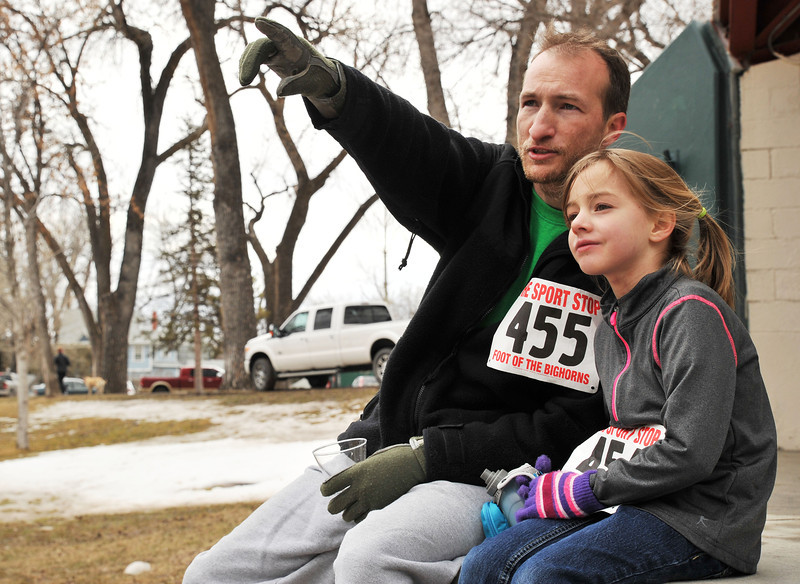 """Jon Fiskum and 6-year-old daughter Emma Fiskum sit on the band shell stage as he points to Emma's mother entering the last stretch of the 5K race during the Sheridan Jaycees """"Run 'Till You're Green"""" fun run event at Kendrick Park."""
