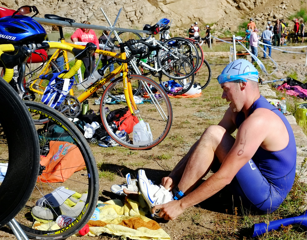 Triathlon competitor Ben Zeller slips on his shoes for the bicycle race after emerging from the lake during the Sibley Lake Triathlon and Duathlon Saturday morning at Sibley Lake near Highway 14 in the Bighorn Mountains. Zeller finished second in the triathlon, which included the 750-meter swim, 13-mile bicycle ride, and a 3.75-mile trail run. Proceeds from the event benefits the Sheridan Area Search and Rescue. The Sheridan Press|Justin Sheely.