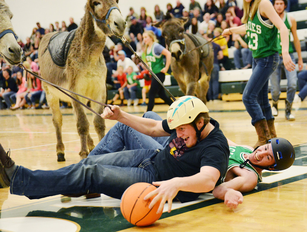 Big Horn student Miles Novak, left, secures the ball from Tongue River's Tyler Kane during the student versus student Donkey Basketball game Thursday at Tongue River High School. Big Horn students and staff competed with Tongue River students and staff in three basketball matches which required the teams to ride Donkeys on the court. Players had to shoot for the basket from the back of the Donkey. Players were only allowed to dismount to make a pass or to retrieve a ball out of bounds, but they still have to hold the reigns of their noble beast, who often refused to cooperate. The Tongue River staff won the first game against Big Horn students followed by a victory by the Tongue River students over the Big Horn staff. The Big Horn students took revenge by earning a victory in the final game against the Tongue River students.