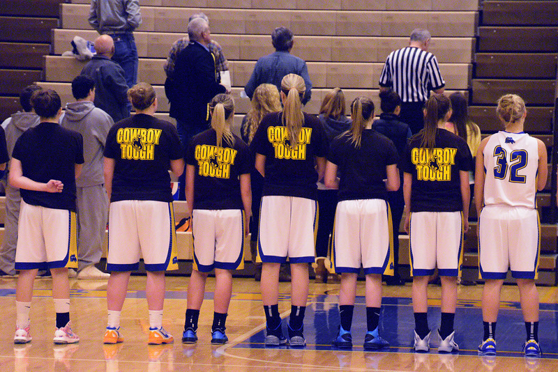 """Lady Broncs players join the crowd in a moment of silence for Weston Johnson, who succumbed to his battle with cancer Friday. Johnson was a former Wyoming football player and coached with the Broncs for one year before he got sick. The Brown and Gold T-shirts were a part of the """"Never Flinch"""" cancer awareness campaign started in his honor. (The Sheridan Press/Brad Estes)"""