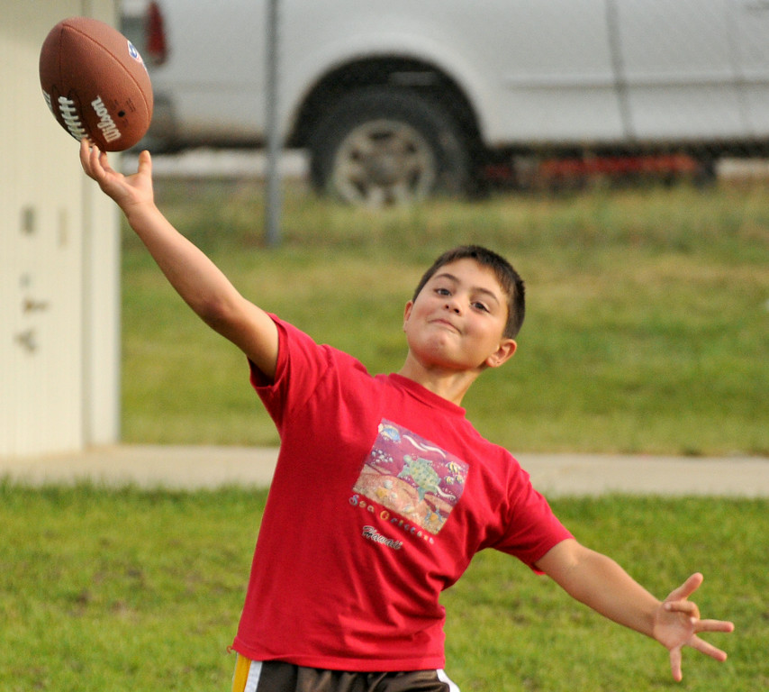Ten-year-old Garrett Scheuber releases the football during the NFL Punt, Pass, and Kick competition on Wednesday at Madia Football Field. The Sheridan Press|Mike Pruden