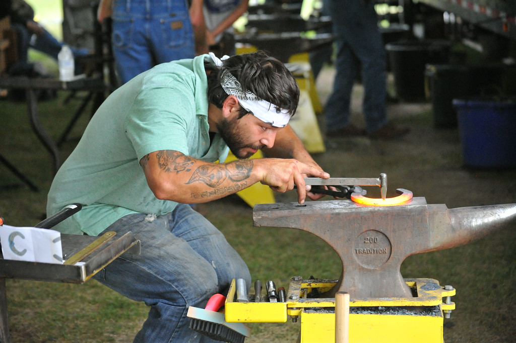 Wade Herda bends down to check his work Sunday at Don King Days for the annual World Championship Blacksmith competition. The Sheridan Press/Kendra Cousineau