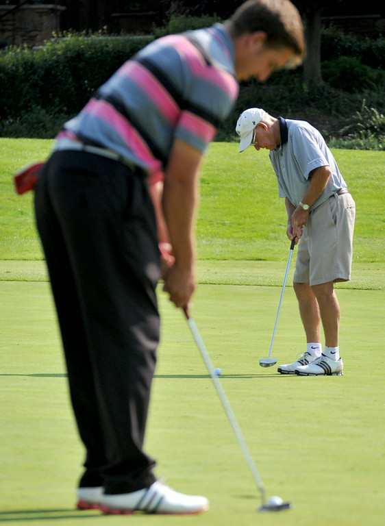 John Kienast, foreground, taps in his par putt as teammate Bruce Holwell takes a few practice strokes next to his ball on Monday at the Rocky Mountain Pro-Am at the Powder Horn. The Sheridan Press|Mike Pruden