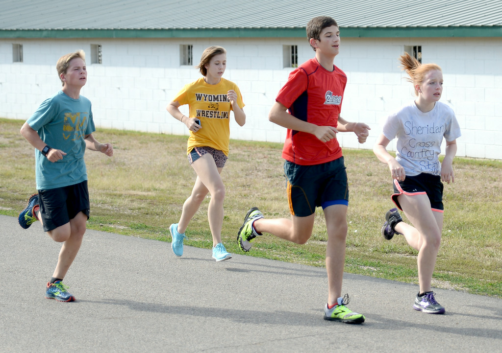 Sheridan High School cross country runners, from left, Finn Bede, Megan Culver, Cooper Neavill, and Elli Sweeney run past the Sheridan County Fairgrounds at practice on Monday. The Sheridan Press|Mike Pruden