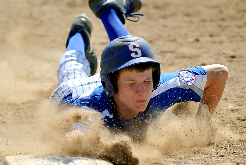 Andrew White dives safely back to first base on an attempted pickoff play on Friday at Thorne-Rider Stadium. White and the Sheridan Babe Ruth All-Stars battled Laramie in the first round of the consolation bracket. The Sheridan Press|Mike Pruden