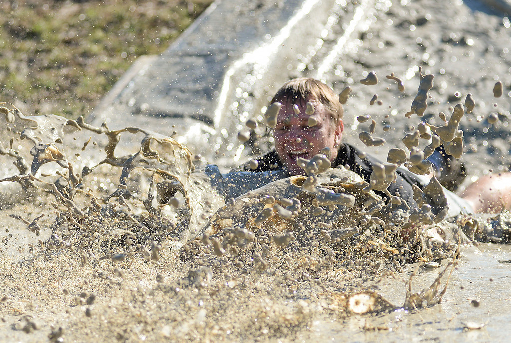Bentonite mud splashes around as Aaron Larson falls down the slide during the Sludge Trudge debut event Saturday at the Sheridan County Fairgrounds. Race participants ran a 5k through a series of obstacles including hay bales and mud pits. The event was inspired by Michelle Maneval after competing in a similar mud racing event last year. Wyo Timing and the Sports Stop organized the event with the Sheridan County Fairgrounds. The Sheridan Press|Justin Sheely.