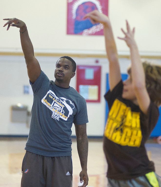 Former Wyoming Cowboy player Brandon Ewing gestures with his hand as students shoot at the basket during the Basketball Clinic Saturday at the Sheridan Junior High School gym. Ewing played point guard for the University of Wyoming Basketball team from 2005 to 2009. After returning to Laramie, Ewing has started a non-profit called 'Brandon Ewing: Once a Cowboy Always a Cowboy' to provide scholarships to help Wyoming high school seniors going to any Wyoming college to purchase books and supplies. Ewing raises money for the non-profit by hosting basketball skill camps in Laramie and across the state.