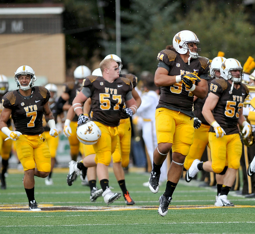 The Wyoming Cowboys, from left, D.J. May, Chase Appleby, Siaosi Hala'api'api, and Alex Borgs, storm the field during pregame intros on Saturday at War Memorial Stadium. The Sheridan Press|Mike Pruden