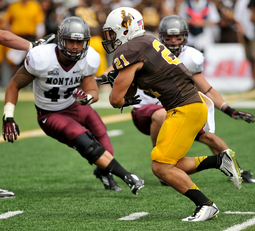 Runningback Shaun Wick tucks the football as he runs past a couple of Montana tacklers during Wyoming's 17-12 victory on Satuday in Laramie. Wick ran for 134 yards in the win. The Sheridan Press|Mike Pruden