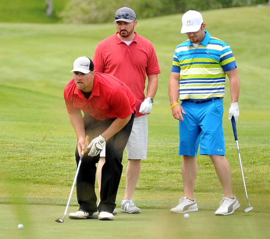 Zach Voithofer, left, lines up his putt as his teammates Joe Prosenick and Joe Stilwell look on during the Chris LeDoux Spurs and Spikes Memorial Golf Tournament on Saturday at the Powder Horn. The Sheridan Press|Mike Pruden