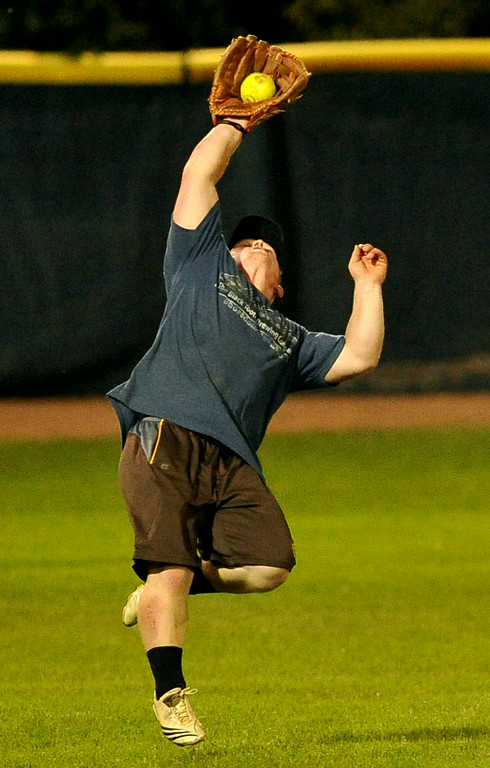 Casey Garnhart makes a leaping catch during the men's softball league championship on Saturday at Thorne-Rider Stadium. The Sheridan Press|Mike Pruden