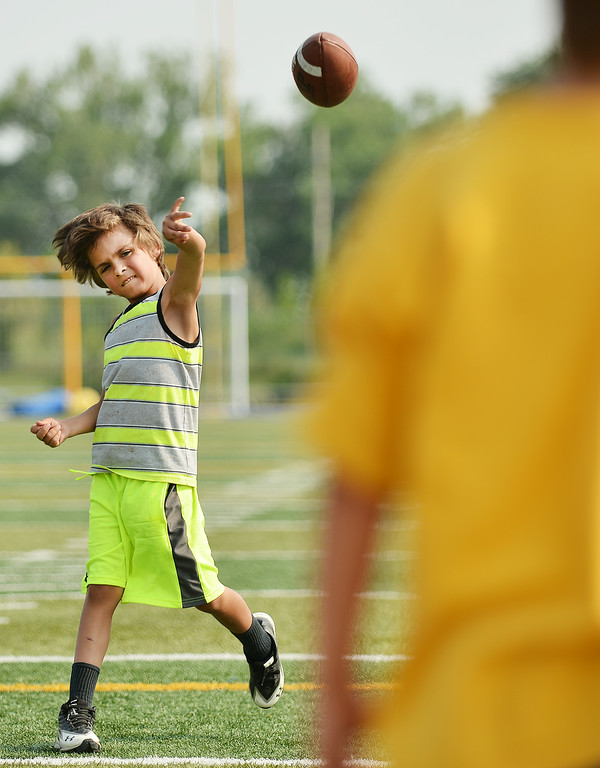Seven-year-old Mason Morris tosses the football to another student during the SHS Football camp Friday on the Homer Scott Field at Sheridan High School. The Sheridan Press|Justin Sheely.