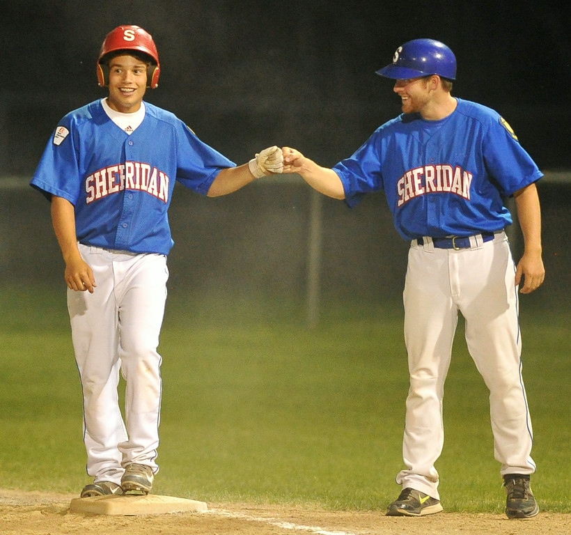 Sheridan Jets coach Cole Gustafson, right, fist bumps Blake King after a single during the Jets round-one rout of the Casper Roughnecks on Thursday at Thorne-Rider Stadium. The Sheridan Press|Mike Pruden