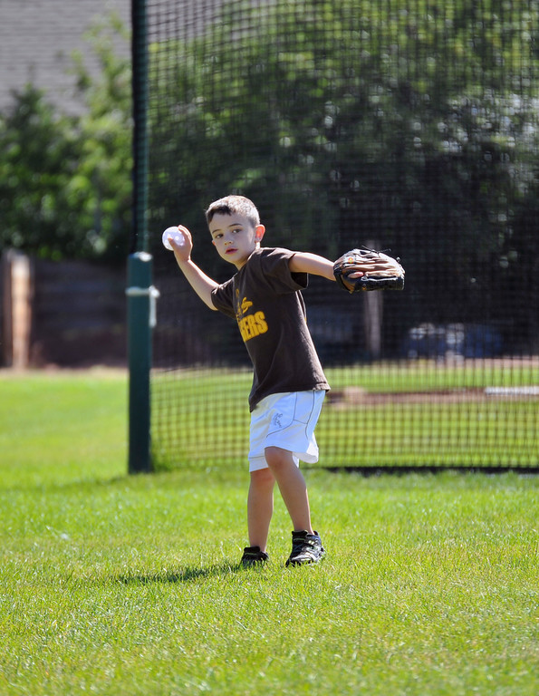 Seven-year-old Daniel Newman plays some baseball of his own with friends during Sunday morning's tournament game. The Sheridan Press/Kendra Cousineau