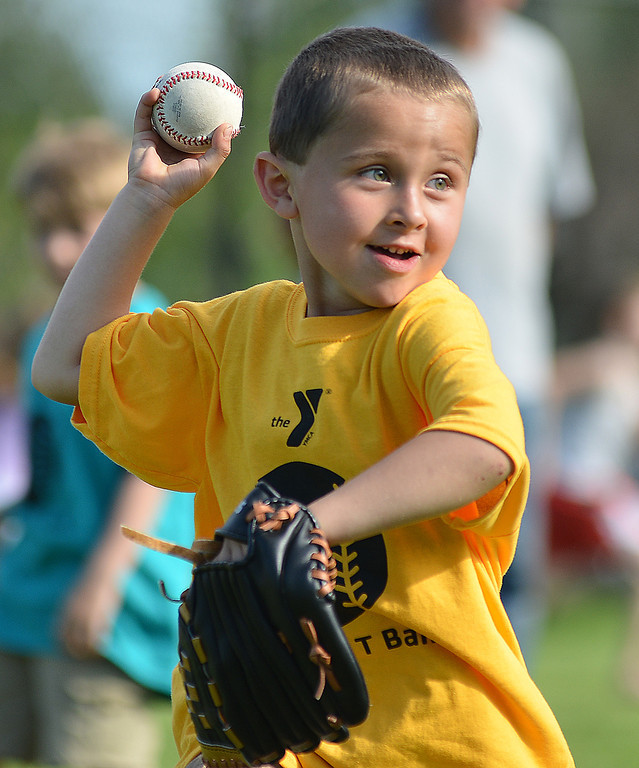 Four-year-old Jayden Thomas throws the ball to first base during the opening day of Itty Bitty T-Ball Tuesday at the Sheridan YMCA.