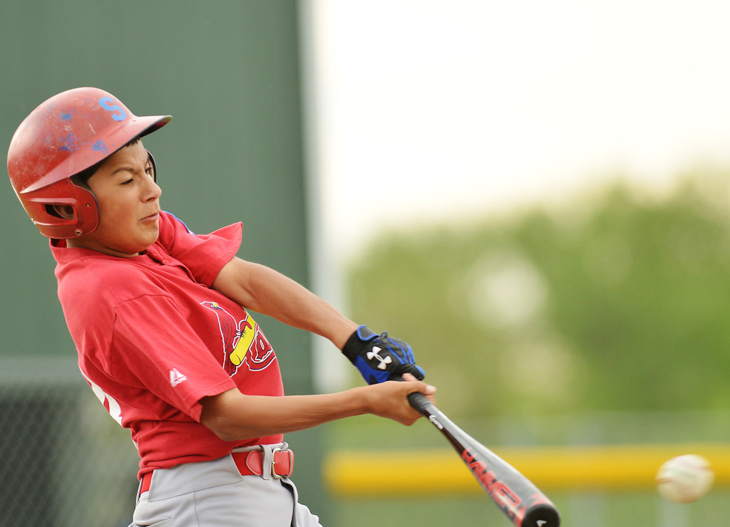 Cardinals player Matthew Roma swings at the ball during the Sheridan Babe Ruth League game Tuesday evening at Redle Field.