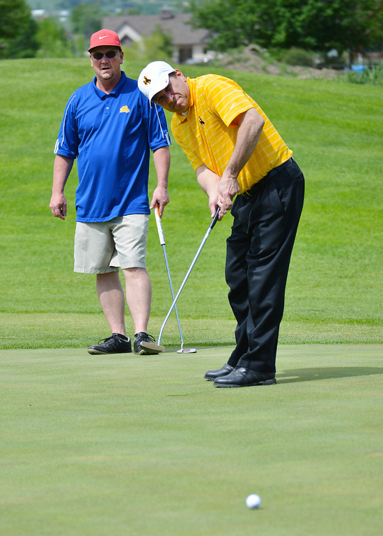 Pat Kiser, left, watches as Alumni Director of the University of Wyoming makes a putt during the Cowboy Joe Golf Tournament Saturday at the Powder Horn Golf Course.